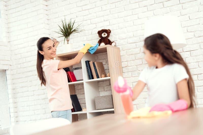 Mamman och dottern gör ren hemma Torka hyllorna och tabellen arkivbilder