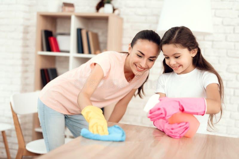 Mamman och dottern gör ren hemma Torka hyllorna och tabellen royaltyfri fotografi