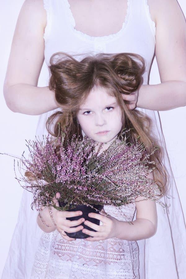 Mamman och dottern i vita klänningar på en vit bakgrund visar vinter, och våren och att rymma blommor och fattar med sidor royaltyfri fotografi
