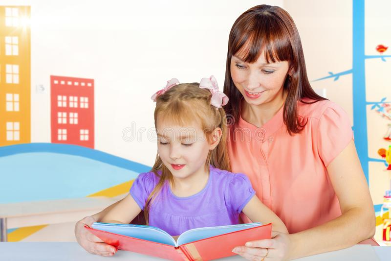Mamman och dottern läste en bok arkivfoton