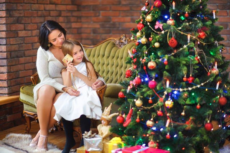 Mamman och dottern sitter nära ferieträdet och betraktar gåvor fotografering för bildbyråer