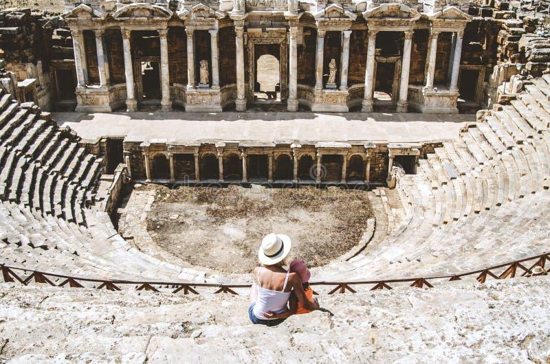 Mamman och dottern sitter på momenten av en forntida amfiteater som lokaliseras i Hierapolis, Pamukkale, det Denizli landskapet royaltyfri foto