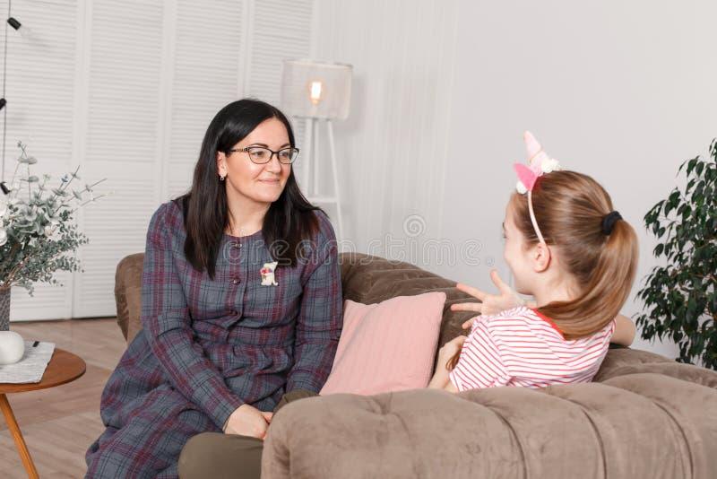 Mamman och dottern sitter på soffan och prata Flickatonåringen med sinnesrörelser berättar hennes moder en berättelse Dottern del arkivfoto