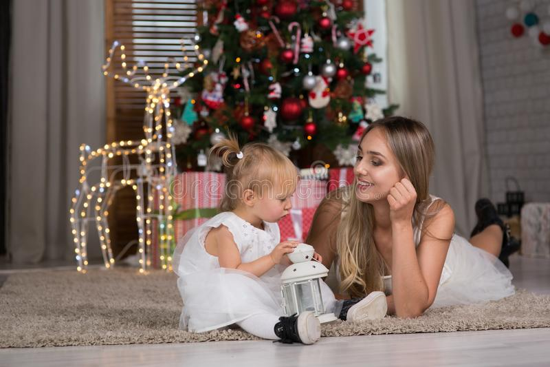 Mamman och dottern sitter runt om julgranen royaltyfria bilder