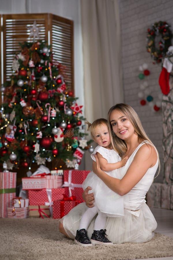 Mamman och dottern sitter runt om julgranen royaltyfri bild