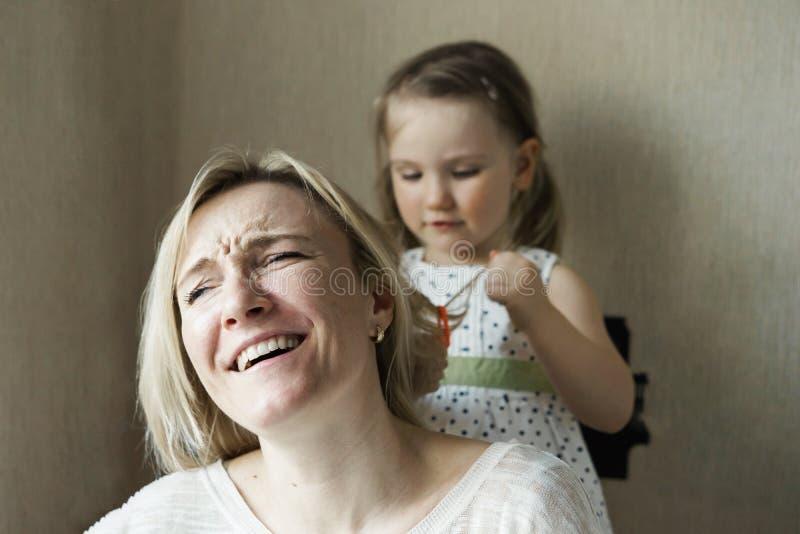 Mamman och dottern sitter vid f?nstret royaltyfri foto