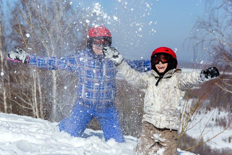 Mamman och dottern, skidar in utrustninglek med snö fotografering för bildbyråer