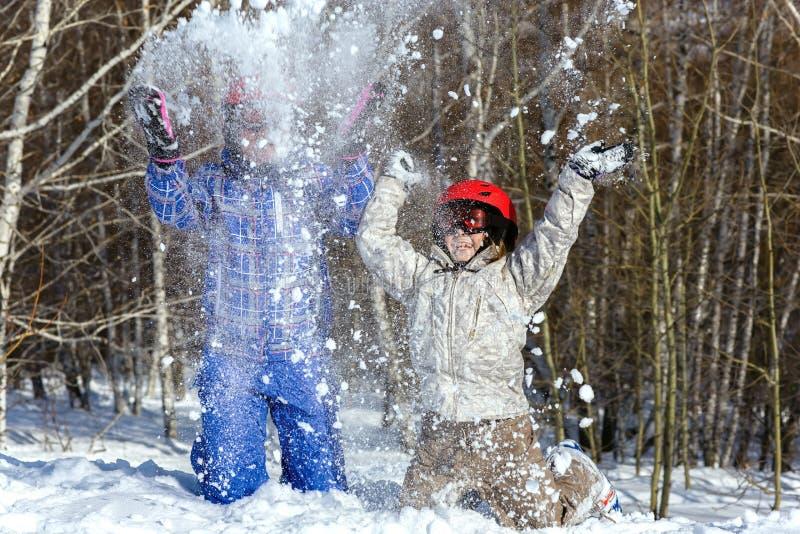 Mamman och dottern, skidar in utrustninglek med snö royaltyfri fotografi