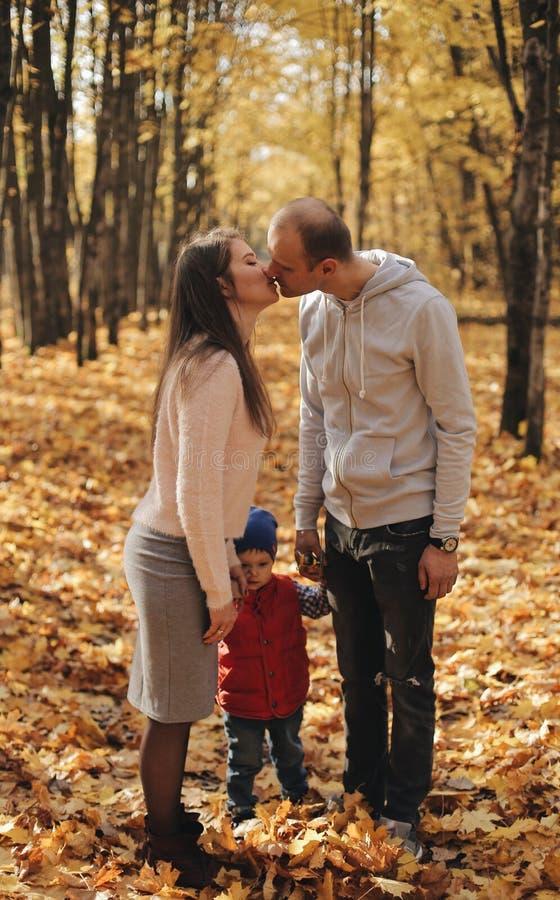 Mamman och farsan kysser sig Son mellan föräldrar lycklig familj royaltyfri bild