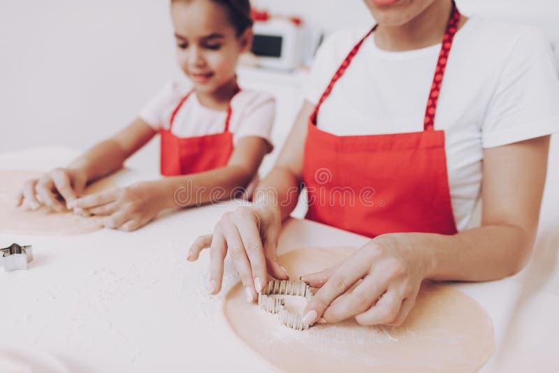 Mamman och flickan lagar mat tillsammans med deg baka caken fotografering för bildbyråer