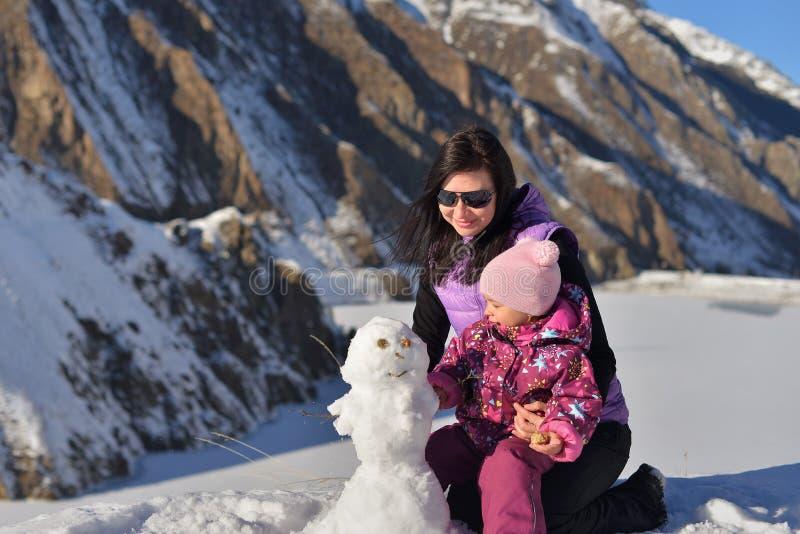 Mamman och hennes lilla dotter i vintern hugger en snögubbe i bergen royaltyfria foton