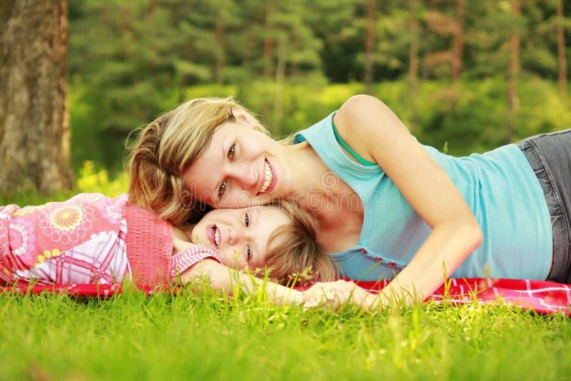 Mamman och hennes lilla dotter ligger på gräset royaltyfri bild