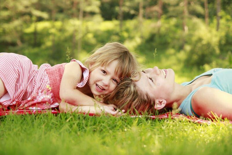 Mamman och hennes lilla dotter ligger på gräset royaltyfria bilder