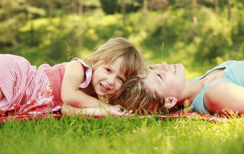 Mamman och hennes lilla dotter ligger på gräset royaltyfria foton