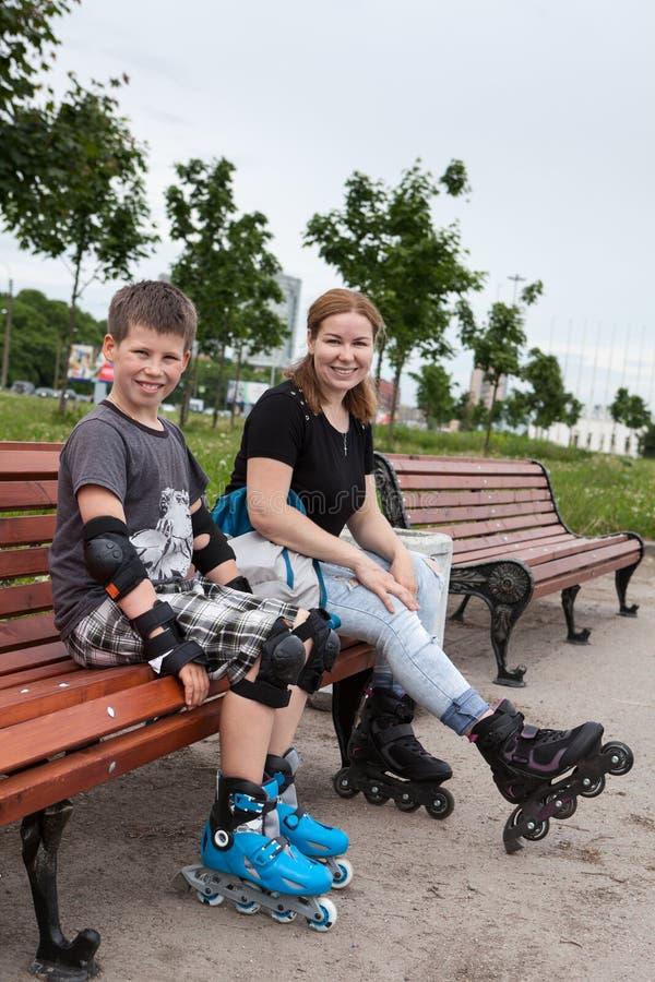 Mamman och hennes son är att sitta som kopplar av på en bänk under rollerblading i parkera fotografering för bildbyråer