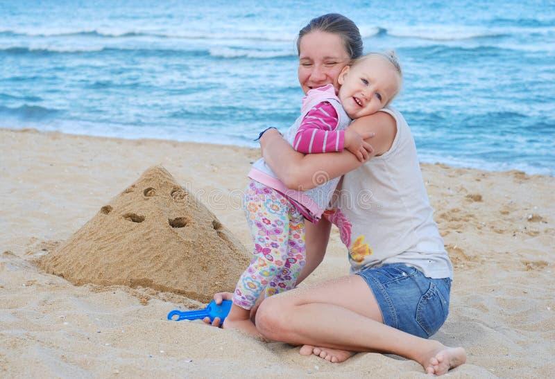 Mamman och lilla flickan bygger sandslottar på stranden Mamman kramar dottern nära havet royaltyfria bilder