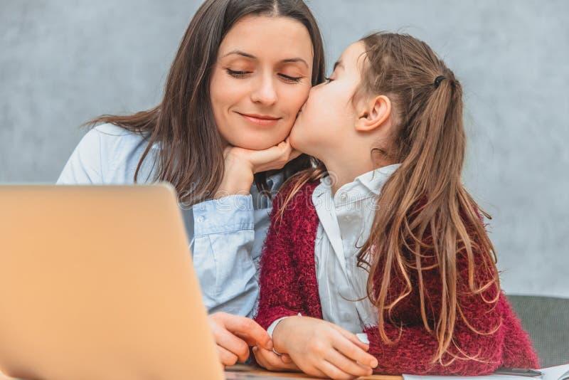 Mamman och skolflickan sitter p? tabellen Närbild av moders ögon som stänger sig på ögonen av hennes dotter ?rligt royaltyfri fotografi