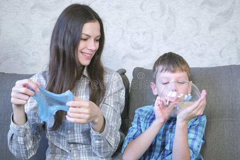 Mamman och sonen blåser upp stora bubblor från slammar Lek med slam royaltyfria bilder