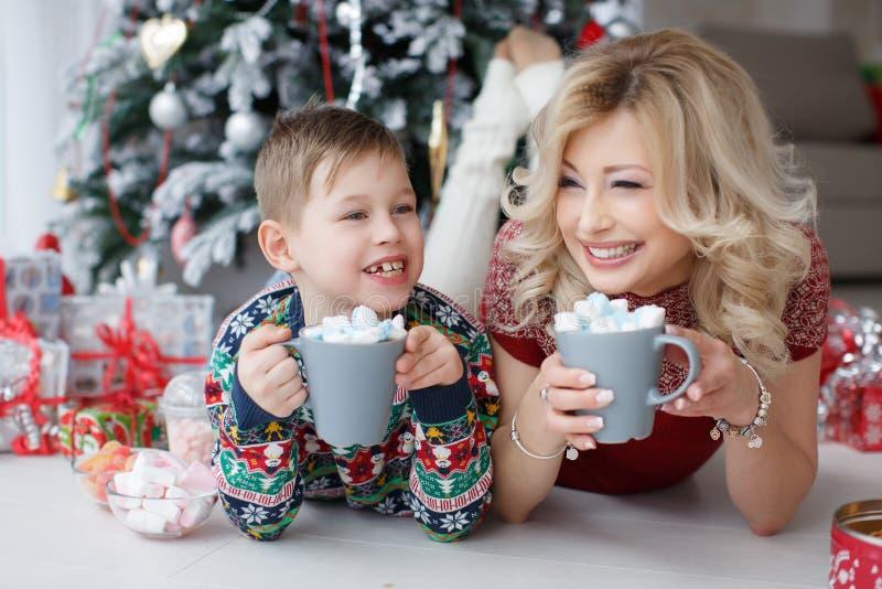 Mamman och sonen ligger nära trädet för det nya året med stora koppar av cappuccino och marshmallower royaltyfri bild
