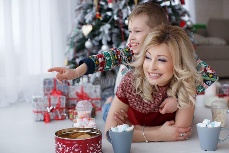Mamman och sonen ligger nära trädet för det nya året med stora koppar av cappuccino och marshmallower arkivfoton