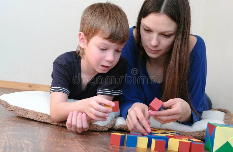 Mamman och sonen som tillsammans spelar den träkulöra utbildningsleksaken, blockerar att ligga på golvet arkivfoton