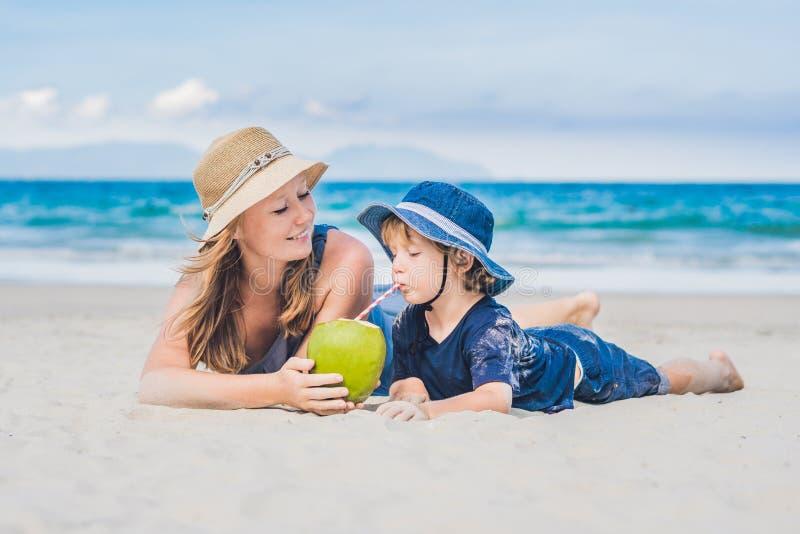 Mamman och sonen tycker om strand- och drinkkokosnöten arkivbild