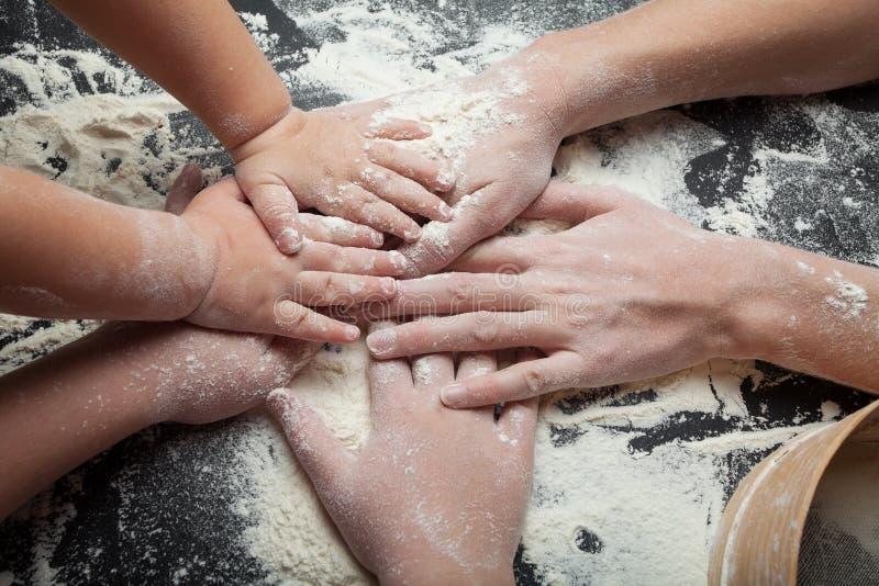 Mamman och två döttrar förbereder hemlagade kakor, festliga kakor och den hemlagade kakan fotografering för bildbyråer