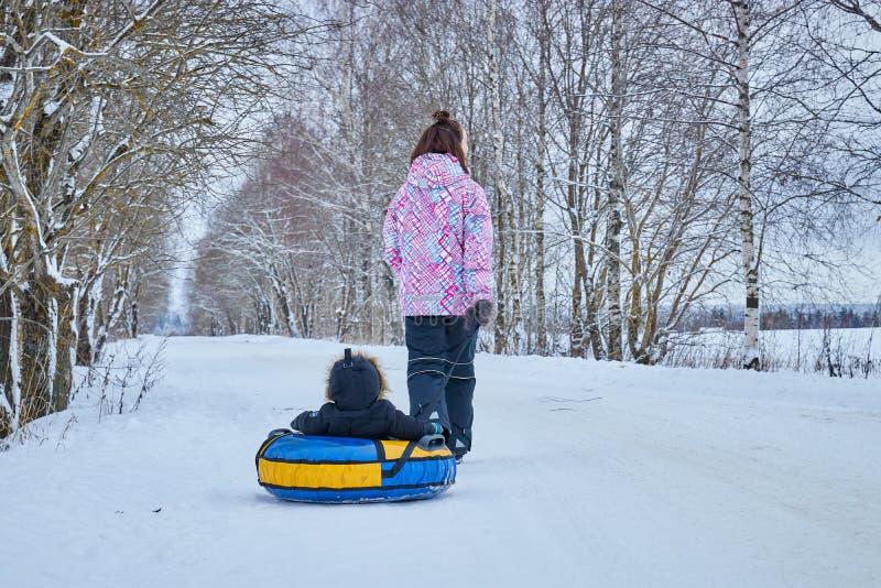 Mamman rullar hennes lilla son på rör i parkerar i vintern lycklig familj utomhus vintergyckel för unga barn royaltyfri bild