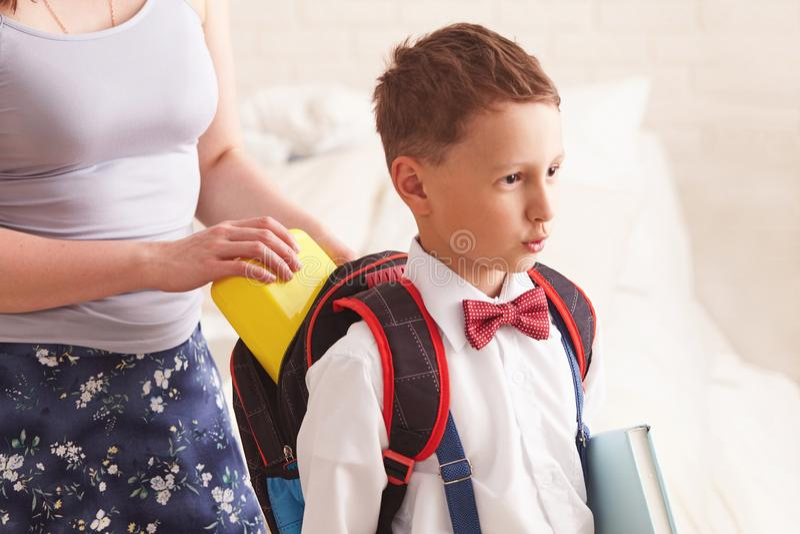 Mamman sätter en packad skolalunch i en plast- ask för hennes son royaltyfria bilder