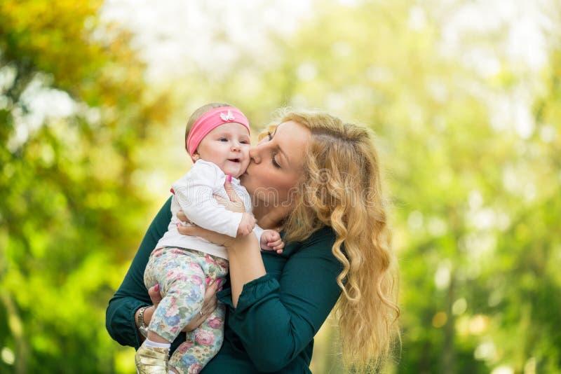 Mamman som kysser hennes dotter, behandla som ett barn royaltyfri bild
