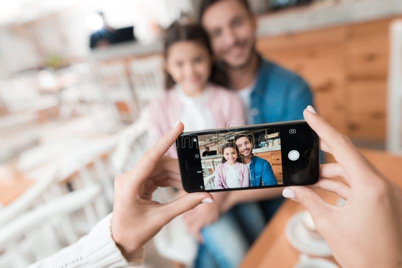 Mamman tar bilder av hennes familj på smartphonen royaltyfria foton
