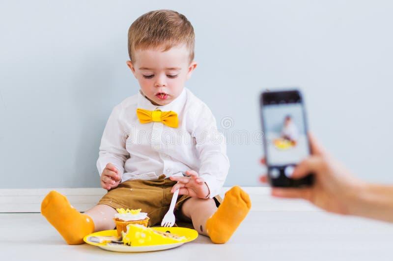 Mamman tar ett foto eller en video på telefonen, som hennes son äter kakan arkivfoto