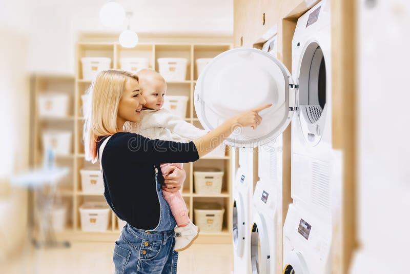 Mamman visar hennes dotter en tvagningmaskin royaltyfri bild