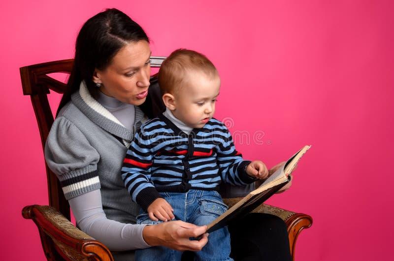 Mammason som läser en bok som sitter i en tappningstol royaltyfria foton