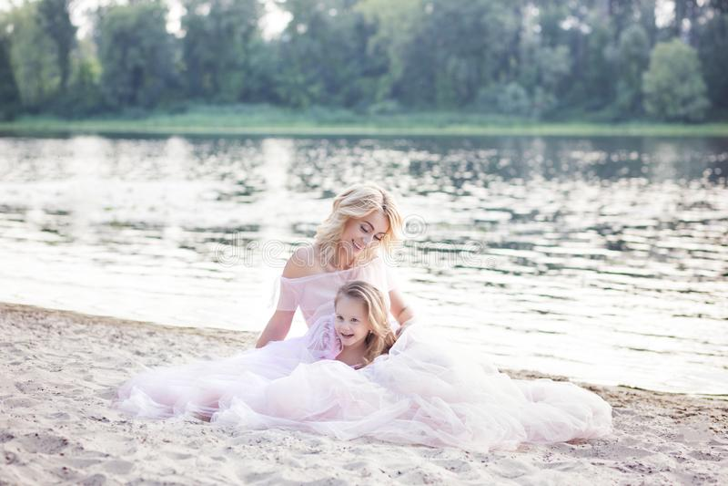 Mammaspelen met haar kind op een vakantie door het meer Familielevensstijl en liefdeconcept Moeder en dochter die tedere ogenblik stock afbeelding