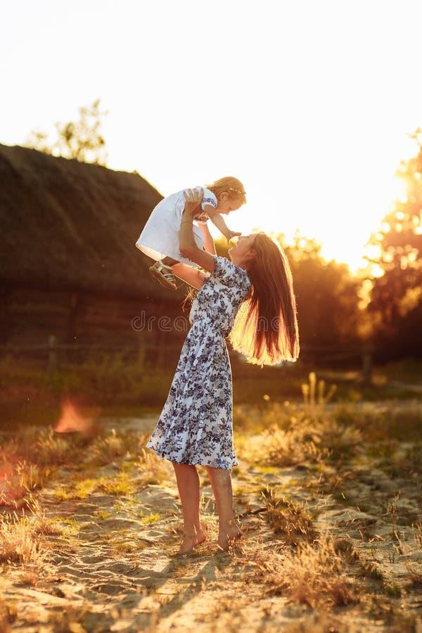 Mammaspelen met haar weinig dochter, gelukkige vrouw die met meisjesdochter geniet van die haar houdt omhoog opheffend in haar wa royalty-vrije stock fotografie