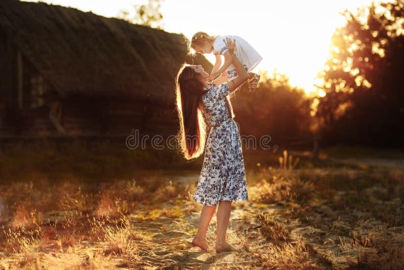 Mammaspelen met haar weinig dochter, gelukkige vrouw die met meisjesdochter geniet van die haar houdt omhoog opheffend in haar wa stock afbeelding