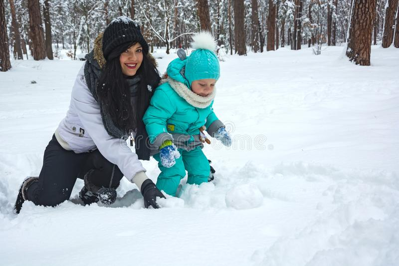 Mammaspelen met het kind in de sneeuw royalty-vrije stock fotografie