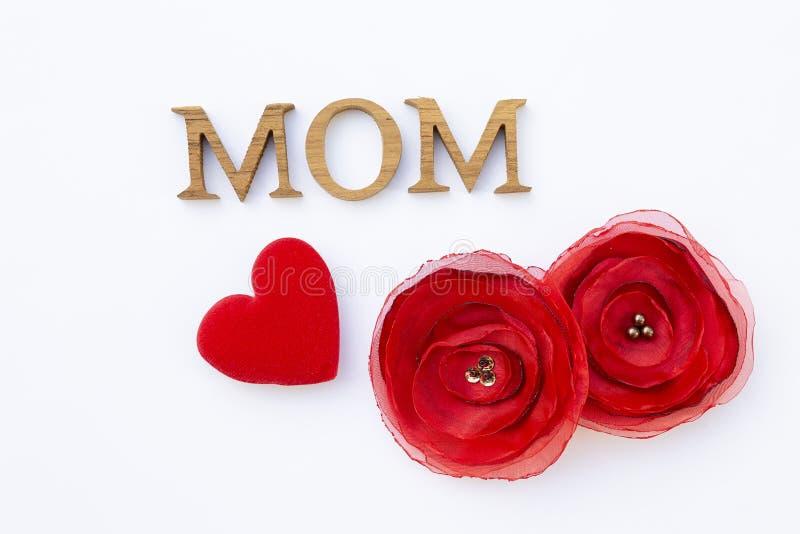 Mammasteg trätext med rött tyg blomman och den röda hjärtaisolaten på vit bakgrund fotografering för bildbyråer