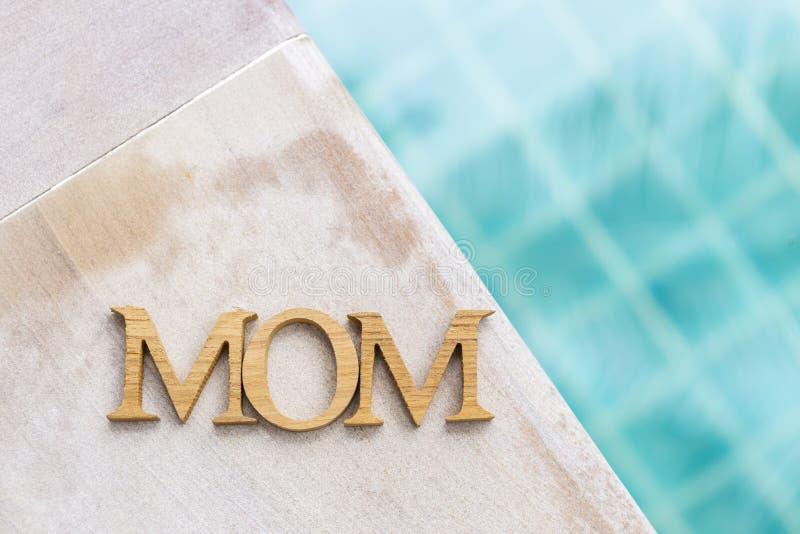 Mammaträtexturbokstav på simbassängkanten med utrymme på suddig bakgrund för blått vatten arkivfoton