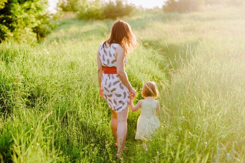 Mammauppehälledotterns hand och går gå på naturen i solnedgångljus royaltyfri fotografi