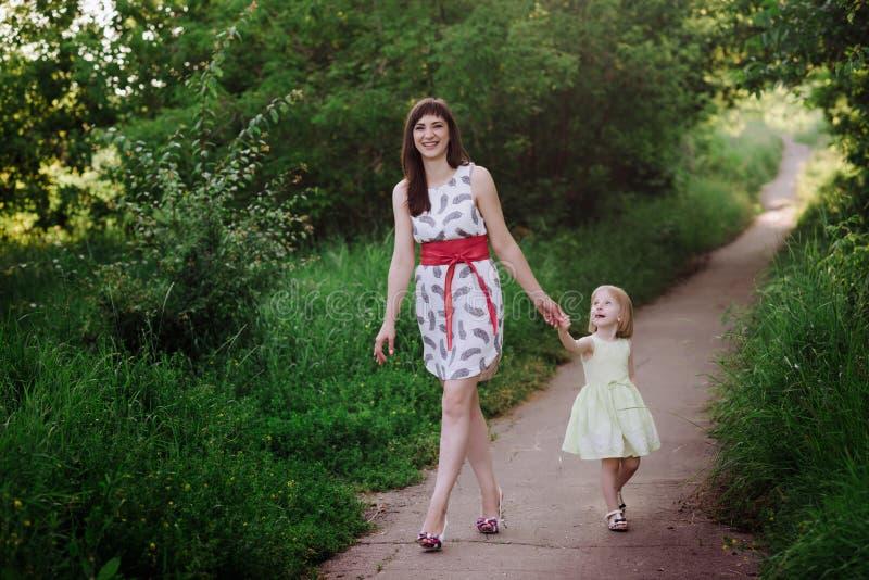 Mammauppehälledotterns hand och går gå på naturen i solnedgångljus royaltyfria bilder