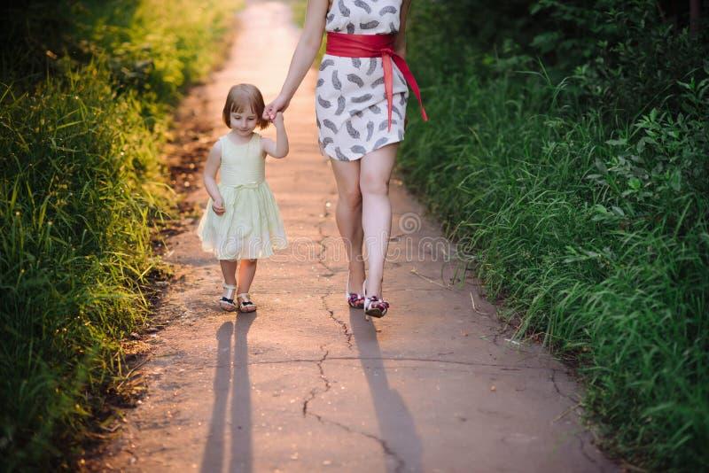 Mammauppehälledotterns hand och går gå på naturen i solnedgångljus arkivfoto