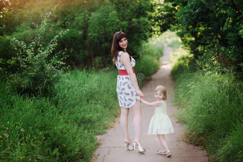 Mammauppehälledotterns hand och går gå på naturen i solnedgångljus arkivfoton