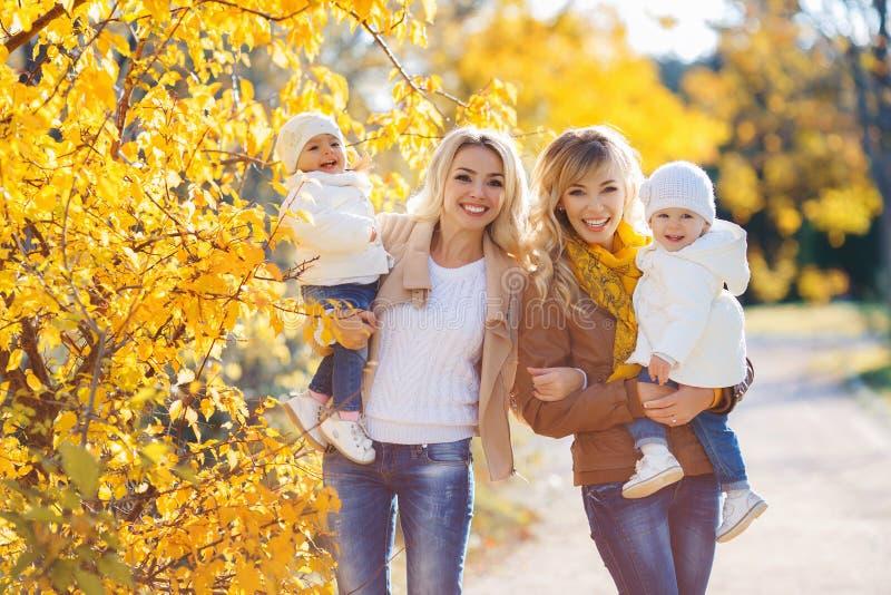 Mamme e bambini per una passeggiata nel parco in autunno fotografie stock