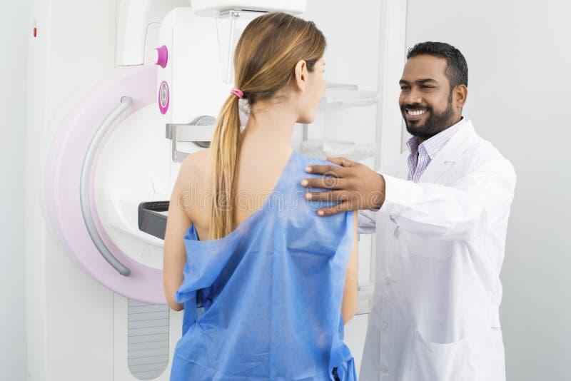 Mammogramprov för doktor Preparing Patient For royaltyfri foto