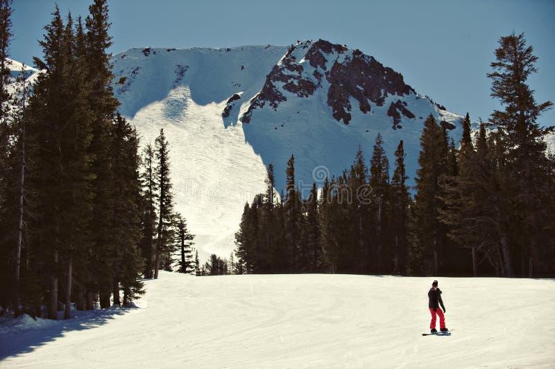 Mammouth Mountain. Solo snowboarder beneath the peaks of Mammoth Mountain stock photo
