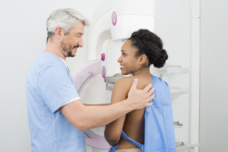 Mamograma que experimenta paciente sonriente Te del doctor Looking At Female fotos de archivo