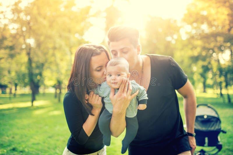 Mamuś i ojczulka mienia dziecko 3 miesiąca stary nowonarodzonego i całowanie, on Szczęśliwa rodzina z ojcem, matką i niemowlakiem obrazy royalty free