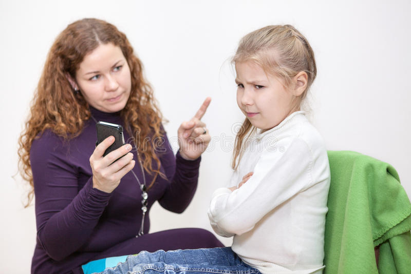 Mamy łajania dziecko dla przeglądać nieodpowiednią zawartość na twój smartphone obrazy stock